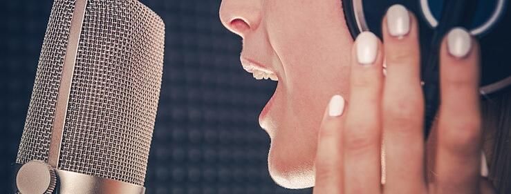 An adult voice actor records in a studio